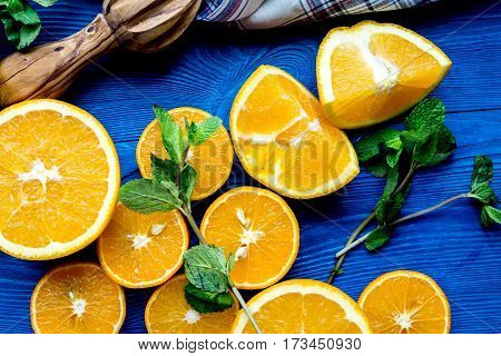 cut oranges with fresh mint leaves and towel on blue kitchen table top view
