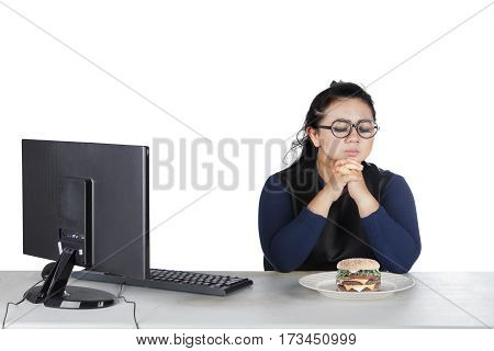 Portrait of obesity woman works with computer and hesitate to eat donuts on the studio