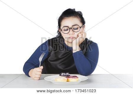 Image of obese female holds fork and hesitate to eat donuts isolated on white background