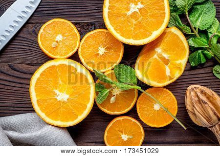 fresh orange juice squeezing on dark wooden kitchen table background top view