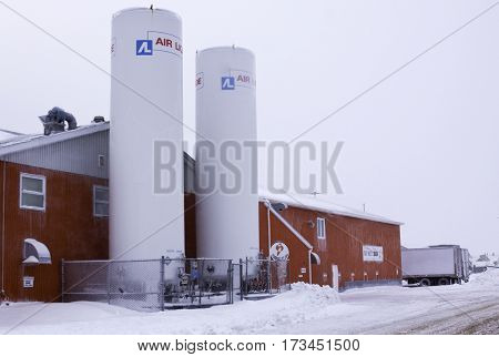 Caraquet, New Brunswick, February 5, 2017 -- Close up of a large fish processing building with two large upright tanks at Caraquet, New Brunswick on a chilly overcast day in February.