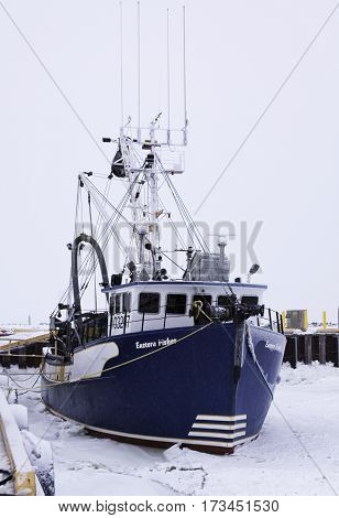 Caraquet, New Brunswick February 5 2017 -- Close up from the front of large colorful fishing boat at the snow covered docks in the frozen waters of Chaleur Bay at Caraquet New Brunswick on a chilly overcast day in February.