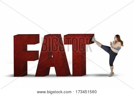 Overweight woman kicking word of fat in the studio isolated on white background