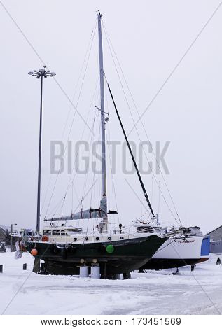 Caraquet, New Brunswick, February 5, 2017 -- Vertical of fishing sail boats dry docked for the winter in the snowy land off the frozen waters of Chaleur Bay at Caraquet, New Brunswick on a chilly overcast day in February.