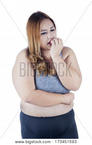 Picture of overweight woman standing in the studio while wearing sportswear and looks confused