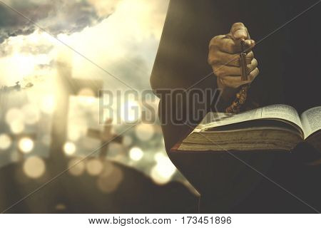 Devout christian person praying with a bible and rosary shot with crucifix symbol on the background