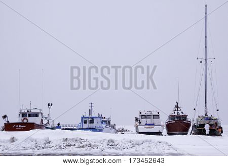 Caraquet, New Brunswick, February 5, 2017 -- Horizontal of fishing boats dry docked for the winter in the snowy land off the frozen waters of Chaleur Bay at Caraquet, New Brunswick on a chilly overcast day in February.