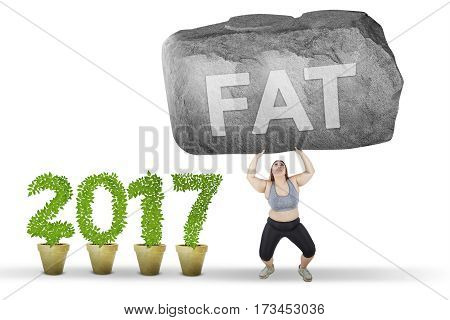 Young woman lifting a big stone with a fat word and wearing sportswear near number 2017 isolated on white background