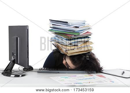 Businesswoman sleeping on the keyboard with stack of documents over her head isolated on white background