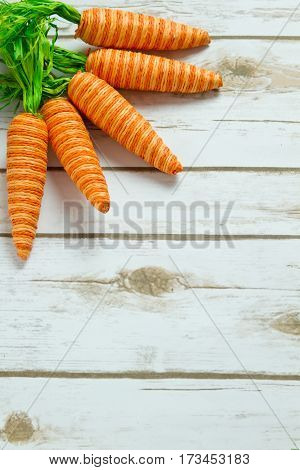 Orange striped faked carrots on a rustic whitewashed wood background with room for text