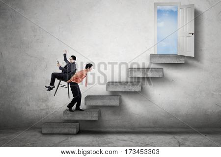 Male worker walking on the stair while carrying his boss through a doorway
