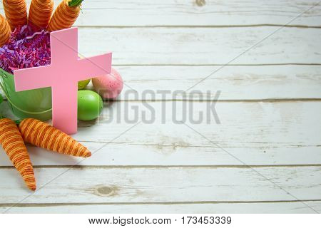 Pastel Pink Christian Cross, Orange striped faked carrots and colorful Easter Eggs on a rustic whitewashed wood background with room for text