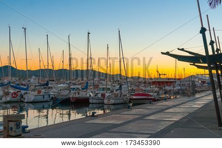 Sailboats & small yachts in Ibiza marina harbour in the evening.  Magnificent golden warm sunset at the end of the day.