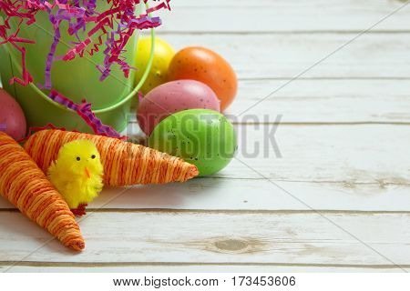 Orange striped faked carrots and colorful Easter Eggs with a spring chick on a rustic whitewashed wood background with room for text