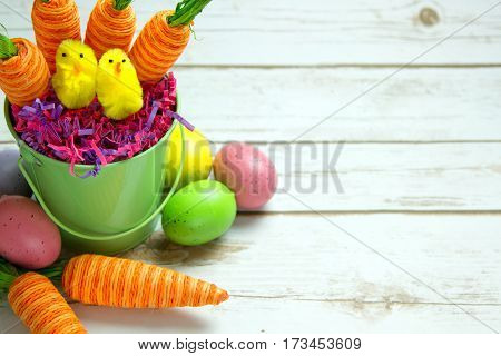 Orange striped faked carrots and colorful Easter Eggs with a spring chicks on a rustic whitewashed wood background with room for text