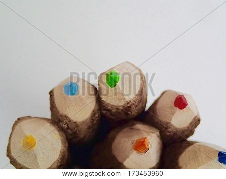 Rustic colored pencils in a pile on a white background.