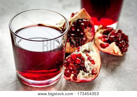 fresh slices of pomegranate with red juice in glasses on kitchen table background