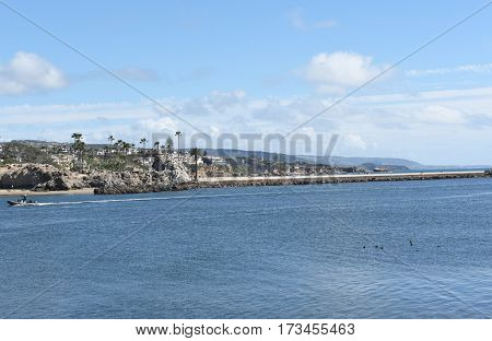 NEWPORT BEACH, CALIFORNIA - FEBRUARY 22, 2017: Small boat passses by Corona Del Mar homes along the Newport-Avalon Channel in Southern California, viewed from the Newport jetty.