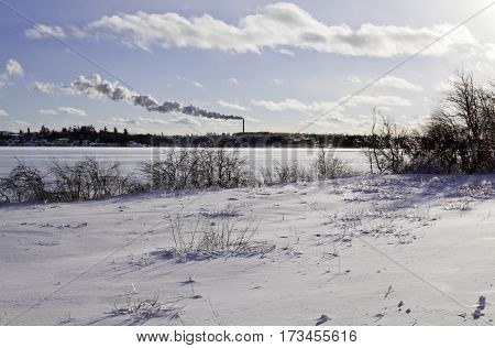 Winter snow scene, snow covers a small field of bare branches and bushes are covered in thick ice from a recent ice storm. In the distance across the frozen Miramichi River, an industry billows smoke, shot in New Brunswick, on a chilly bright, blue sky