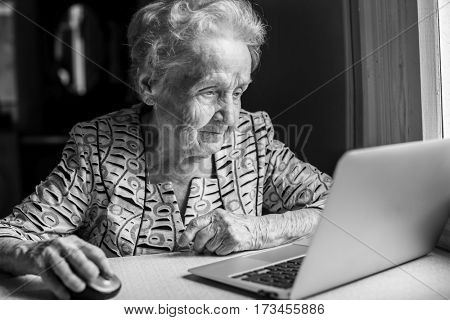 An elderly woman with a laptop. Black-and-white photo.