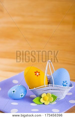 Colorful Easter Eggs In Basket With Flower On Fabric On Wooden Background