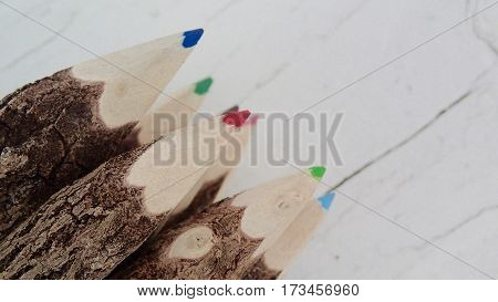 Bunch of colored pencils on a rustic white background