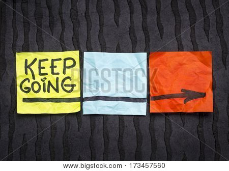keep going - motivation or determination concept - handwriting on colorful sticky notes against black lokta paper