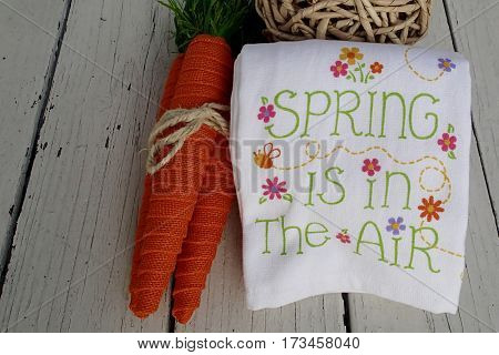 Cute spring towel on a rustic wood background with colorful carrots