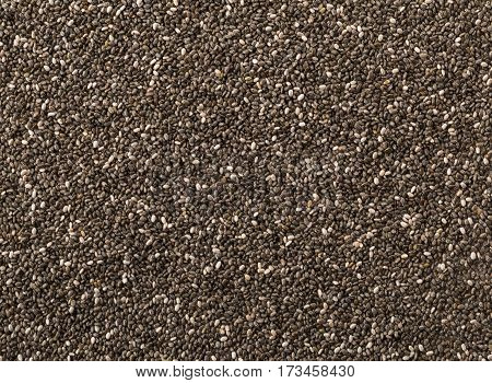 Raw unprocessed dried black chia seeds frame filling texture background