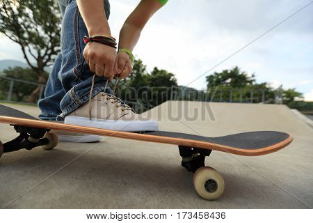 young skateboarder tying shoelace on skateboard at skatepark ramp