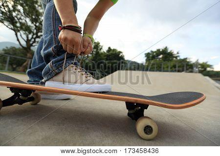 young skateboarder tying shoelace on skateboard at skatepark ramp
