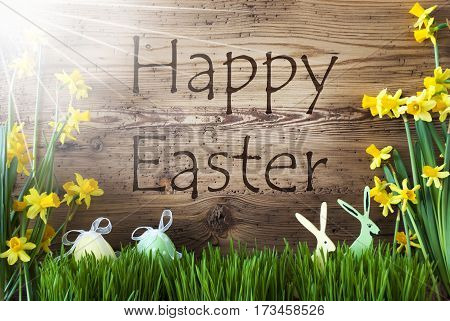 Wooden Background With English Text Happy Easter. Easter Decoration Like Easter Eggs And Easter Bunny. Sunny Yellow Spring Flower Narcisssus With Gras. Card For Seasons Greetings