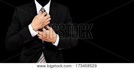 Businessman touching necktie, isolated on black background with copy space