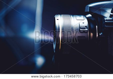 Digital Camera and the Photography Concept Photo. Dark Blue Color Grading with Little of Light. Camera Side View.