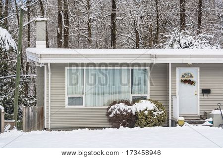 Entrance of residential house with front yard in snow. Family house on winter cloudy day