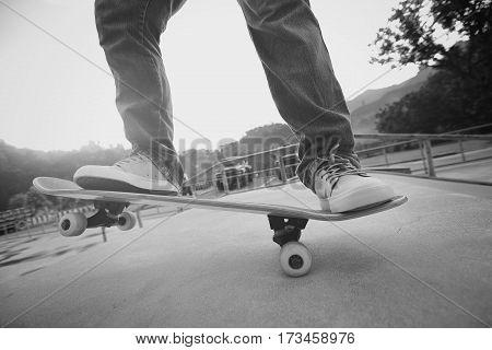 young skateboarder legs practice ollie at skatepark ramp