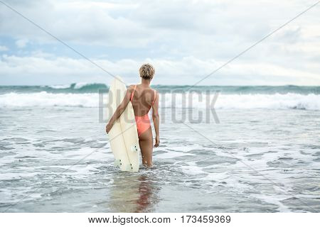 Pretty blonde girl with short hairstyle stands backsides in the waves on the beach on the background of the sea and the cloudy sky. She wears orange swimsuit and holds the surfboard. Horizontal.