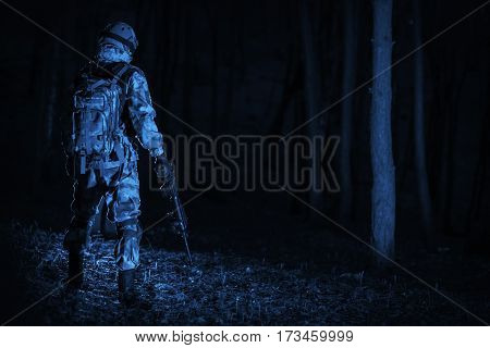 Military Operation at Night. Dark Blue Color Grading Concept. Soldier with the Rifle Staying Back in the Middle of the Pitch Dark Forest.