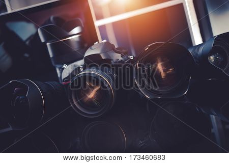 Pro Photography Technology. Professional Digital Photography Studio Equipment. Digital DSLR Camera and Few Prime Lenses on Glassy Desk.