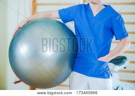 Caucasian Male Rehabilitation Specialist with Ball Awaiting Next Patient. Rehabilitation Center.