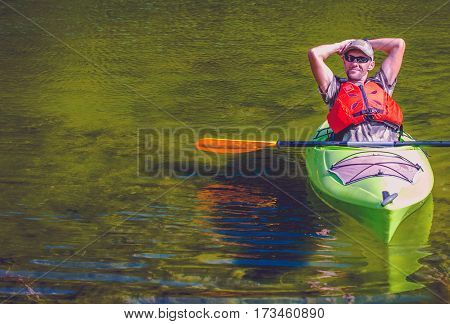 Relaxed Kayaker on the Lake. Caucasian Sportsman. Water Sports and Recreation Concept.