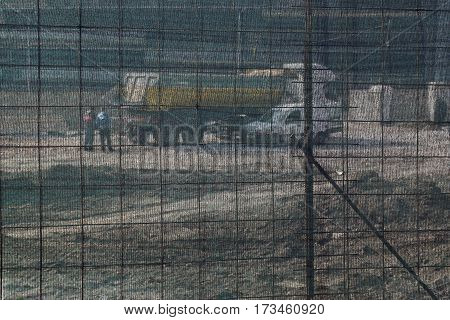 Unrecognizable Workers And Truck At Construction Site Behind Safety Net