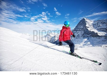 Young attractive caucasian skier with ski on ski slope in famous Swiss Jungfrau ski resort, Grindelwald, Switzerland