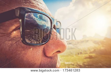 Sunglasses Protection. Caucasian Men in His 50s in the Trendy Black Sunglasses. Closeup Photo. Mountains Reflection in the Lenses.