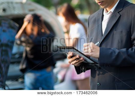 Side view of Asian insurance agent writing on tablet while examining car after accident