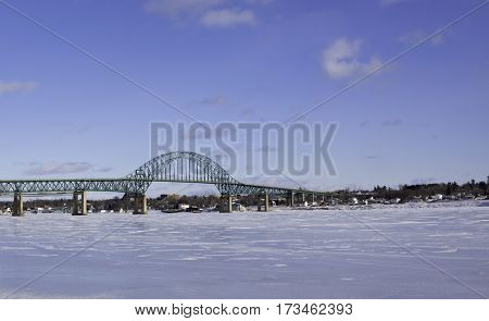 Winter snow scene Centennial Bridge crossing over the Miramichi River New Brunswick to Chatham with buildings and commerce in the background on a chilly bright blue sky sunny day in February.