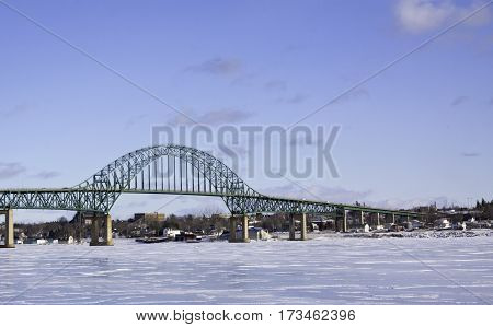 Winter snow scene, Centennial Bridge crossing over the Miramichi River, New Brunswick to Chatham with buildings and commerce in the background on a chilly bright blue sky sunny day in February.