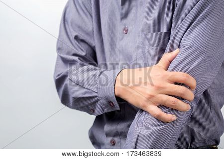 Man suffering from chronic joint rheumatism. Elbow pain and treatment concept.