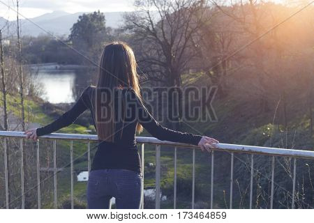Young Woman Standing On A Balcony, Looking At The Nature.