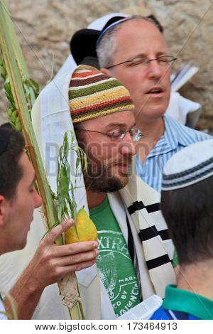 JERUSALEM, ISRAEL - SEPTEMBER 20, 2013: The Western Wall of the Temple in Jerusalem. Young religious Jew in a knitted skullcap and talite with citrus-etrog praying in the morning of Sukkot